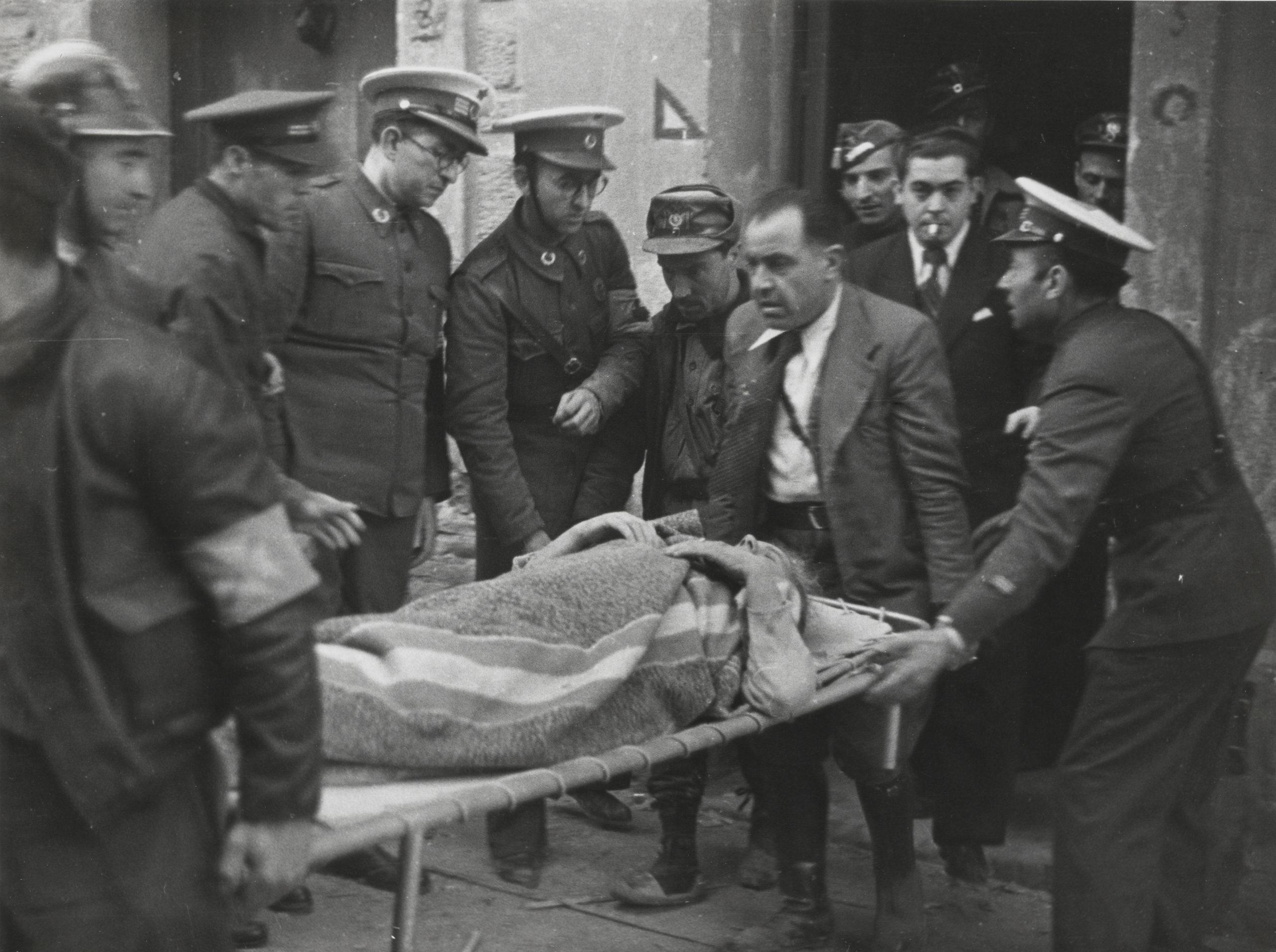 A l'esquerra un bomber de Barcelona ajudant en el desallotjament de ferits a causa d'un bombardeig al Poble Sec el 16/03/1937