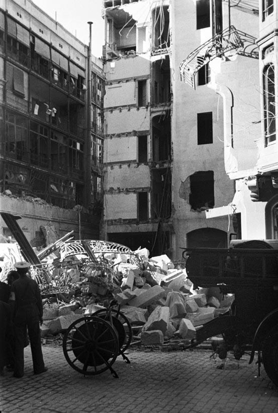 Edifici bombardejat i carro portamànegues i part posterior d'un vehicle de bombers.